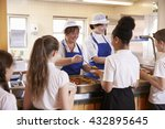Stock photo two women serving kids food in a school cafeteria back view 432895645