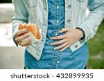 Young Woman Eating Fast Food...