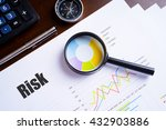 "Small photo of Magnifying glass on colourful pie chart with ""Risk"" text on paper, dice, spectacles, pen, laptop calculator on wooden table - business, banking, finance and investment concept"