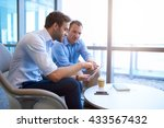 Two Businessmen Sitting In A...
