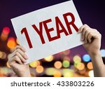 Small photo of 1 Year placard with night lights on background