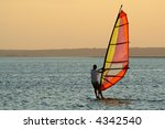 Backlit windsurfer at sunset on calm coastal water - stock photo