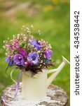 Small photo of Garden stile summer bouquet. Mix of lilac and purple anemone flowers, geranium flowers and heuchera or alumroot leaves. Bouquet in decorative watering can. Garden stile wedding bouquet. Flower design.