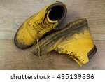 Muddy Work Boots On A Wooden...