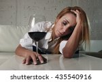 Small photo of blond sad and wasted alcoholic woman sitting at home sofa couch drinking red wine holding glass sleeping drunk looking depressed lonely and suffering hangover in alcoholism and alcohol abuse