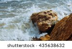 Small photo of Tide and sea, sand and rocks, beach under cloudy skies. Slider shot featuring a sand beach and surf hitting the rocks. Sparkling ocean sea water waves surface & coastal rock reef coast surge shore.