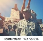 A military soldier is standing in front of an army tank vehicle with sun outside for an American war, defense or security concept.