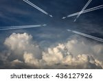 Small photo of Multiple airplane creating exhaust contrails across a blue cloudy sky for the concept of a crowded airspace.