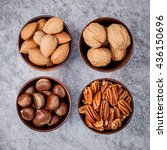 Small photo of Whole almonds,whole walnuts ,whole hazelnut and pecan nuts in wooden bowl setup with stone background.