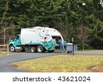 A Sanitation Worker dumps a trash can into a garbage truck. - stock photo