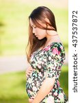 Small photo of Pretty young woman looking down adoring her pregnant stomach in a beautiful green park background