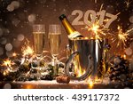 Small photo of New Years Eve celebration background with pair of flutes and bottle of champagne in bucket and a horseshoe as lucky charm