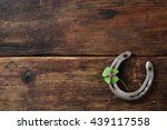Stock photo old horse shoe with clover leaf on rustic wooden background 439117558