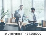Small photo of Asking for professional advice. Two young businessmen in smart casual wear talking and gesturing while leaning at the window sill in office