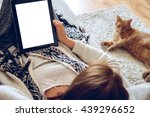 Stock photo woman in home cozy clothes lying on a sofa using tablet with headphones looking at a lazy red cat 439296652