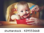 mother feeding her baby boy... | Shutterstock . vector #439553668