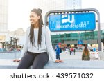 Black young woman portrait in Berlin. She is sitting on a concrete wall in Alexanderplatz with ubahn, the underground train, sign on background.