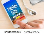 Small photo of Hand touch smart phone and ear phone with Promo code word on wood table ,Internet marketing concept.