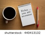 Small photo of Relax, you are awesome - reminder or positive affirmation words - handwriting on a notebook with cup of coffee