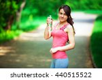 a girl drinks water after sport | Shutterstock . vector #440515522