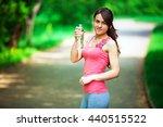 a girl drinks water after sport | Shutterstock . vector #440515522
