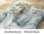 Small photo of Back pocket Jean. Money in blue socket. Bucks in hip trap .Ragged blue trousers and smackers - dollars.