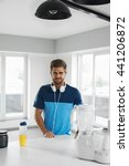 Small photo of Sports Energy Drink. Handsome Healthy Happy Man With Fit Muscular Body In Sportswear, Headphones With BCAA Amino Acid Beverage And Bodybuilding Nutrition Supplements In Kitchen Before Fitness Workout