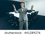 Young happy business man in suit in modern corporate conference room - stock photo