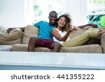 Small photo of Young couple watching television while relaxing on the sofa