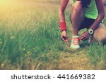 Stock photo young woman runner tying shoelace on nature trail 441669382