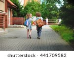 Small photo of Boy and girlie go to school having joined hands. Warm September day. Good mood. Behind backs at children satchels. The girlie laughs. Back to school. Little first grader.