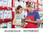 Stock photo woman looking at salesman using digital tablet in pet store 441968365