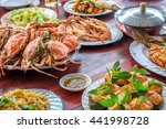 Small photo of Thai style set of seafood insist of Thai steamed curry fish in banana leaf cups decorated with basil leaf, (Hor Mok Pla) steamed crab/prawn/shrimp with seafood sauce