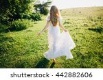 Small photo of Young girl in a white dress in the meadow. Woman in a beautiful long dress posing in the garden. Stunning bride in a wedding dress