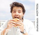 young man eating a hamburger | Shutterstock . vector #442979056