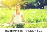 Stock photo young woman enjoying meditation and yoga on green grass in the summer on nature 443374522