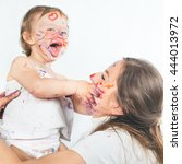 Small photo of Happy mom and baby playing with painted face by paint. Games with child affect early development. Important to spend enough time with your kids.