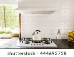Stock photo new style kitchen with dark worktop white gas cooker and decorative brick backsplash 444692758