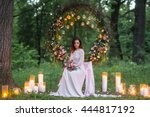 Portrait of a young beautiful dark-haired bride with candles.