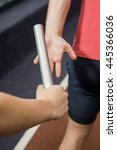 Small photo of Athlete passing a baton to the partner at gym