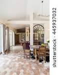 Small photo of Very roomy dining room interior with tiled floor, antique furniture and large terrace windows