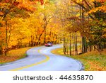 A car on curvy autumn forest road, with motion blur from its speed - stock photo