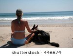 Woman with dog on beach - stock photo