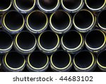 Black and yellow pvc pipes stacked in construction site - stock photo