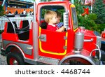 Firetruck in the entertainment park (with kids riding in it) - stock photo