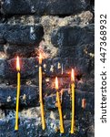 Small photo of Four burning candles on old sooty blackened stone wall