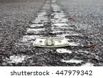Small photo of Crumpled money on a deserted road leading into the horizon for the concept of American dream.