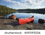A Red Canoe Rests On A Rocky...