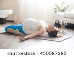 Healthy lifestyle concept. Pregnancy Yoga and Fitness. Young pregnant yoga woman working out with her pet dog in living room interior. Pregnant model lying in reclining hero pose after practice home