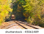 A locomotive on an old track emerges from a wooded locale - stock photo